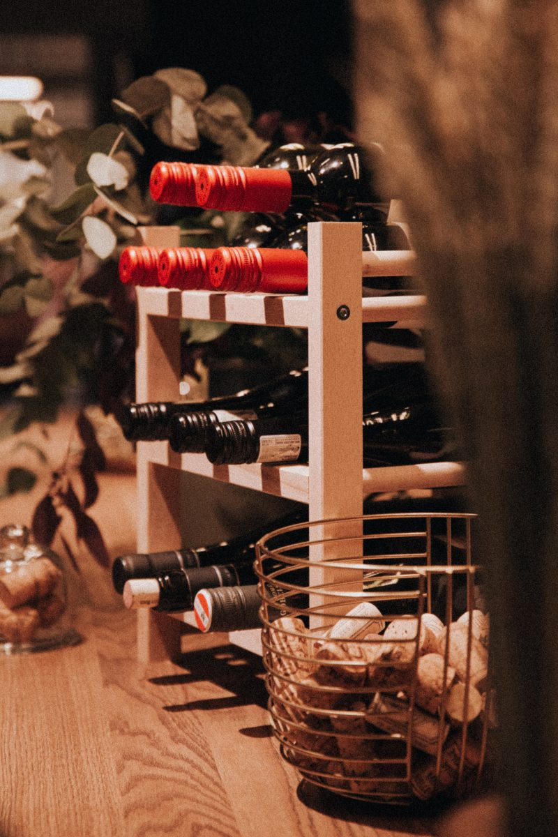 Wine Bottles on a wooden rack with corks in a basket